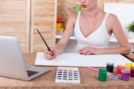 artful: Close up of painting woman with long neck wearing white top. Concept of sketching and artful work in office