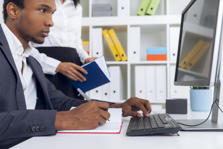 centered: Centered African American guy is looking at computer screen and typing. His colleague is standing beside him Stock Photo