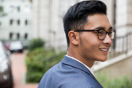Close up of successful Asian businessman wearing glasses at the street of his hometown. Concept of prosperity and personal growth