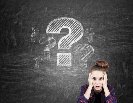 difficult to find: Portrait of hipster girl and giant question marks drawn on blackboard behind her. Concept of big question