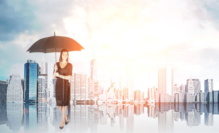 delusion: Woman wearing dress with black umbrella is standing in sunlit city and smiling. Concept of delusion and not paying attention to environment. Toned image