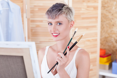 Cheerful artist is holding two paintbrushes and looking to the camera smiling. Concept of good moods and creativity Stock Photo