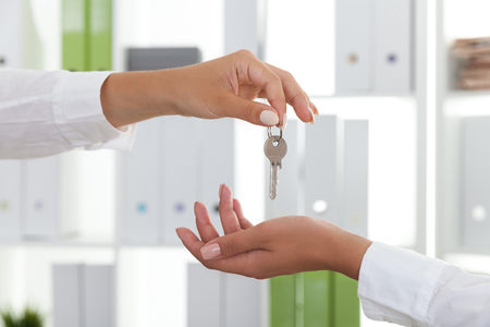 escrow: Woman giving house key to her client in office with green and white folders on bookshelves. Concept of real estate market Stock Photo
