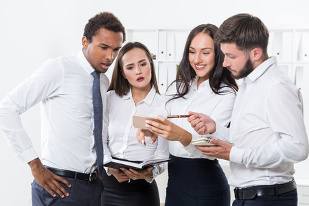 coping: Group of businesspeople coping with a serious crisis and one girl is looking at her cell phone screen demonstrating her ignorance.