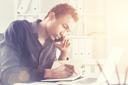 phonecall: Side view of a concentrated african american businessman using notepad and laptop on office desktop while having mobile phone conversation.  Toned image