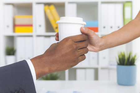 Close up of woman giving paper cup of coffee to her coworker. Concept of office life and little acts of kindness