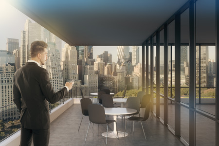 panoramic windows: Businessman standing in blue office with panoramic windows and magnificent cityscape. Concept of successful entrepreneur. Toned image.