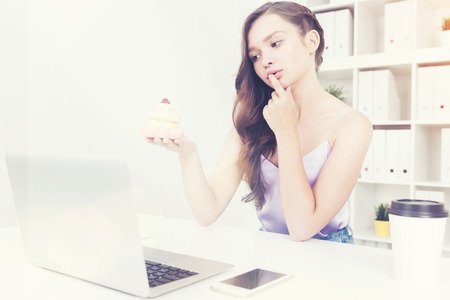 whether: Girl deciding whether to eat cupcake of not while sitting in her office chair near laptop and smart phone. Concept of difficult nutrition choices and challenges of dieting. Toned image Stock Photo