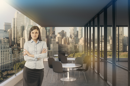 panoramic windows: Businesswoman standing in office with panoramic windows and magnificent cityscape. Concept of successful entrepreneur. Toned image Stock Photo