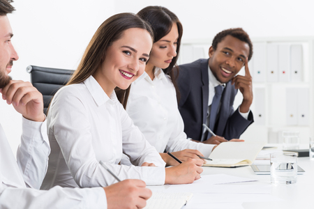 life partners: Portrait of four business partners sitting in row and smiling. Concept of enjoying your life and staying positive Stock Photo