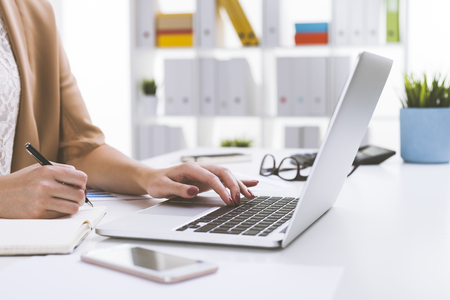 Close up of woman in beige cardigan typing and writing simultaneously. Concept of doing two task and not succeeding Stock Photo