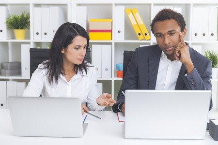 critique: Bored African American guy is looking at computer screen while listening to his bosss critique. Concept of being wrong and not acknowledging it Stock Photo