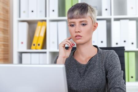 pensamiento estrategico: empleado de oficina pensativo está mirando la pantalla del portátil y pensando en los negocios. Concepto de planificación y pensamiento estratégico Foto de archivo