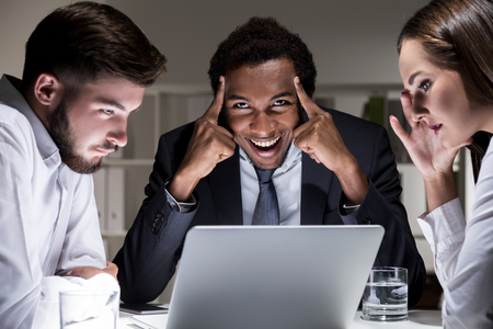 plotting: Group of colleagues are having a secret meeting. One of them is laughing diabolically and plotting treason Stock Photo