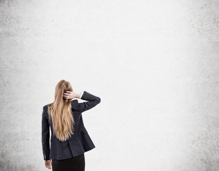 rasa: Woman scratching her head is standing near blank concrete wall and looking at it. Concept of tabula rasa. Mock up