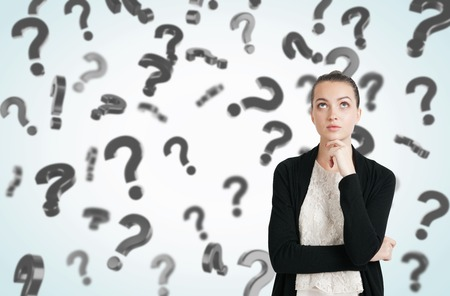 unresolved: Thoughtful young woman with her hand on the chin standing in room full of floating question marks. Concept of solution finding
