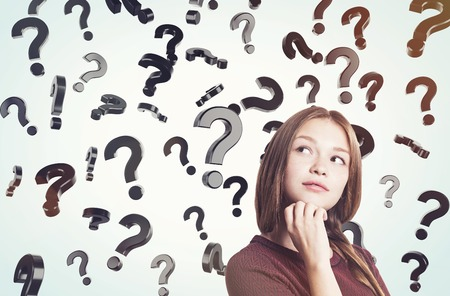 unresolved: Portrait of young woman in brown sweater standing near question marks floating in the air. Concept of looking for the answer. Toned image Stock Photo