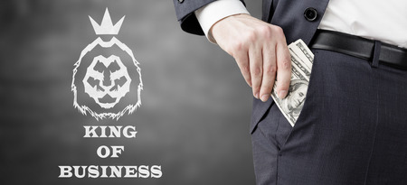 safeness: Close up of businessman putting several dollar bills into his pocket. King of business sketch is depicted beside him. Concept of money laundering