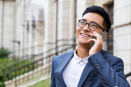 Feliz empresario asiático en gafas está teniendo una conversación telefónica agradable en la gran ciudad. Concepto de comunicación Foto de archivo - 64248578
