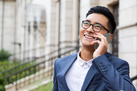 Happy Asian businessman in glasses is having a pleasant phone conversation in large city. Concept of communication