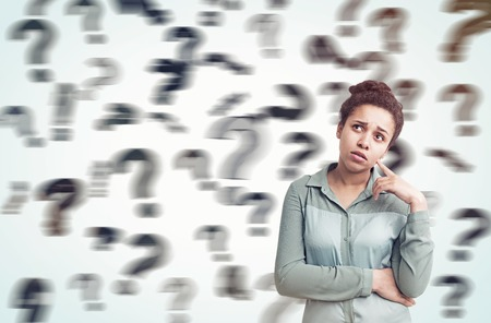 unresolved: African American girl standing in gray room with floating blurred question marks in the background. Concept of decision making Stock Photo