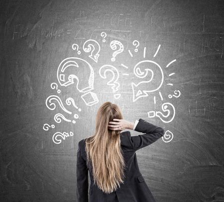 Hintere Ansicht der Frau, die ihren Kopf kratzt und Fragezeichen Skizzen auf Tafel betrachtet. Konzept von zu vielen Fragen
