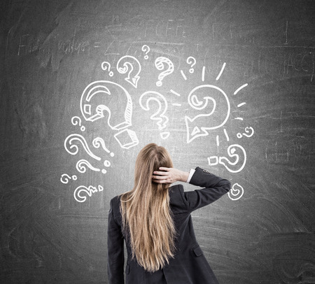 Vue arrière d'une femme se grattant la tête et regardant des croquis de points d'interrogation au tableau. Concept de trop de questions Banque d'images - 64248641