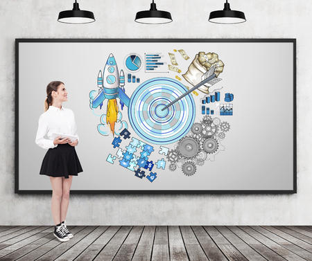 Woman in wide skirt is standing near whiteboard with target sketch on it. Concept of stating your goals and reaching them Stock Photo