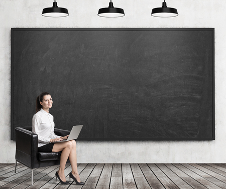 leather armchair: Girl with laptop sitting with her laptop in leather armchair near blank blackboard. Concept of business education. 3d rendering. Mock up Stock Photo