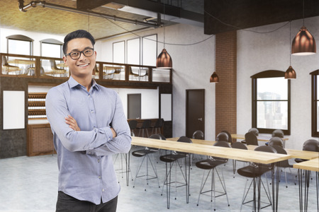 two floors: Asian man standing in restaurant with two floors and long tables with stools. Posters on white and wooden walls. 3d rendering. Mock up. Stock Photo