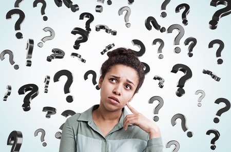 interrogative: African American girl standing in gray room with floating question marks in the background. Concept of decision making