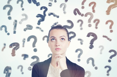 unresolved: Close up of thoughtful young woman with her hand on the chin standing in room full of floating question marks. Concept of solution finding. Toned image Stock Photo