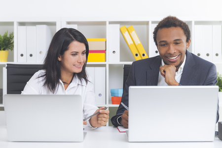 Smiling African American guy is looking at his laptop screen and his colleague is observing his work pleasantly impressed. Concept of work team