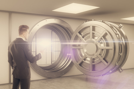 money vault: Rear view of man standing with smartphone near brown bank vault. Concept of money storage. Toned image