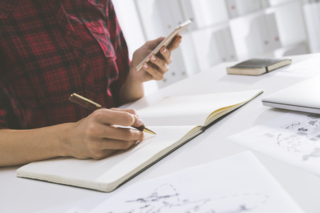 tilted view: Tilted view of womans hands writing in large notebook lying on the talle in white office while she is holding her smartphone. Concept of dying art of handwriting