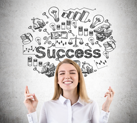 believing: Blond smiling woman with crossed fingers is standing against concrete wall with success sketch on it. Concept of believing in yourself Stock Photo