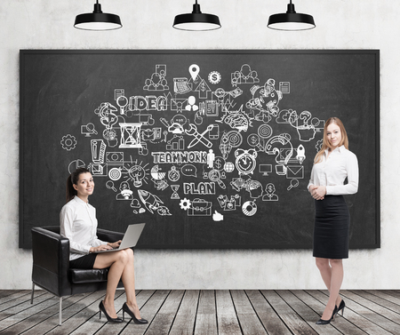 colleague: Girl with laptop sitting near blackboard covered by teamwork icons. Her colleague with coffee is standing near her. Concept of motivational speech giving. 3d rendering Stock Photo