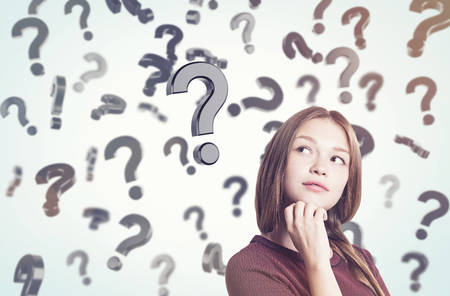 unresolved: Portrait of young woman in braided hair standing near question marks floating in the air. Concept of looking for the answer. Toned image Stock Photo