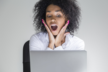 grey eyed: Close up of amazed office employee sitting at her workplace with laptop in room with gray walls. Concept of receiving unexpected news