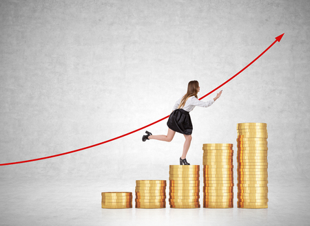 Woman in office clothes running up the stairs made of coins l with red growing graph on concrete wall. Concept of financial career ladder. Mock up