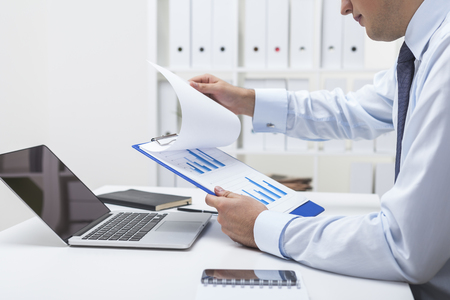 Close up of businessman's hands. He is holding clipboard and checking the data at graph. Concept of statistician's work Foto de archivo