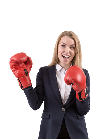 tough luck: Cheerful blond businesswoman in formal clothes and red boxing gloves is standing against white background. Mock up