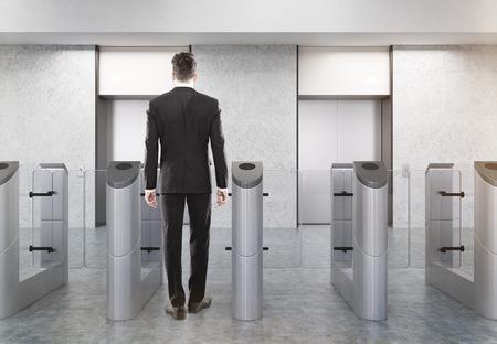 Rückansicht des Mannes am Eingang zum Büro mit Edelstahl-Drehkreuzen und zwei Aufzügen. Konzept der Sicherheit. 3D-Rendering Attrappe, Lehrmodell, Simulation. Standard-Bild - 64409340