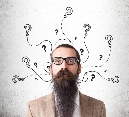 baffled: Baffled man wearing glasses and long beard is standing near concrete wall with question marks crawling out of his head. Concept of too many questions Stock Photo
