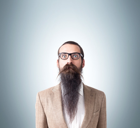 baffled: Baffled man wearing glasses and long beard is standing against gray background. Concept of eccentric person. Mock up Stock Photo