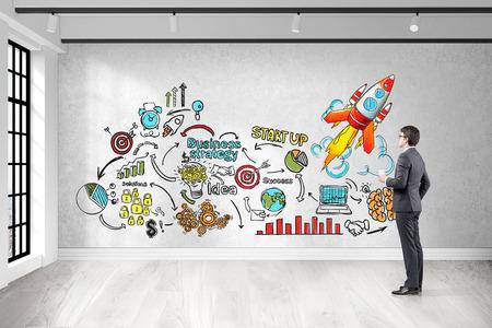 pensamiento estrategico: Vista lateral del hombre de negocios con una taza de café en busca de colores esbozo de inicio en la pared de hormigón. Concepto de pensamiento estratégico. Las 3D.