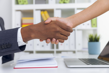 african american handshake: Close up of African American man shaking hand with his his female colleague in office. Concept of meeting