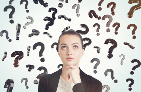 unresolved: Close up of thoughtful young woman with her hand on the chin standing in room full of floating question marks. Concept of solution finding