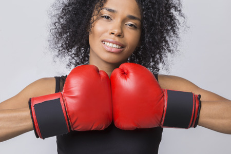 boxing match: Close up of woman in black tank top with muscles in her arms ready to begin her boxing match. Concept of games