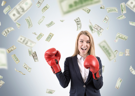 astonishing: Cheerful businesswoman in red boxing gloves is standing against gray background under dollar bill rain. Concept of making money